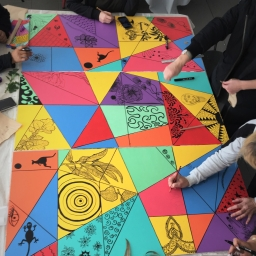 A group of people are creating a colourful mural painting together.